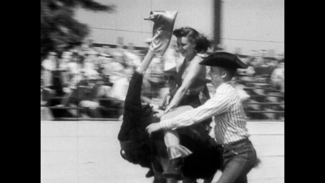 / cowboy helps smiling woman mount blindfolded ostrich / female riders race around the track with some assistance / girl falls off ostrich sprinkles...
