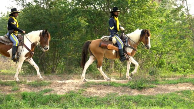 vídeos y material grabado en eventos de stock de 4k cowboy cabalgando en el campo - arma