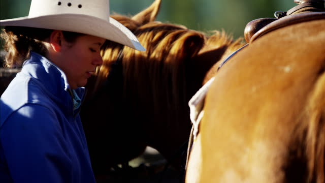 Cowboy in corral saddling horse Dude Ranch Canada
