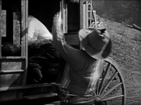 vidéos et rushes de cowboy in hat grabbing man in stagecoach during hold-up / feature - 1924