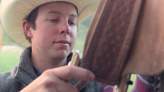 vídeos de stock, filmes e b-roll de caubói inspeciona seu rumo antes selando a andar - ponto de costura