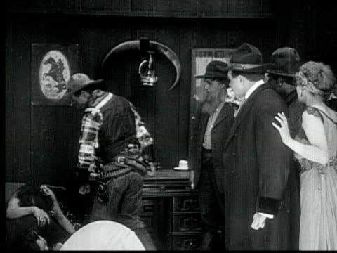 1916 B/W MONTAGE CU MS Cowboy leading crowd, breaking into room, after throwing woman on floor, dragging drunk man outside saloon, 1880s / Santa Monica, California, USA