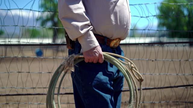 カウボーイはフェンスに身を乗り出し、ロデオアリーナで投げ縄を保持する - ロデオ点の映像素材/bロール