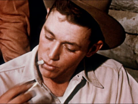 vidéos et rushes de 1950 cowboy lighting and smoking cigarette butt / gunnison, colorado / audio - cool