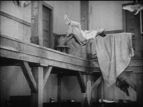 b/w 1924 cowboy (ben turpin) nearly falling off of ledge while sleeping + leaning on chair - tupplur bildbanksvideor och videomaterial från bakom kulisserna