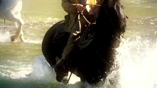 Cowboy on horseback Crossing river in slow motion