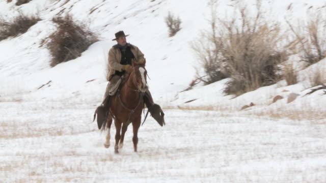 vídeos y material grabado en eventos de stock de pan cowboy on horseback riding with dog up hill to meet horses in snowy landscape / shell, wyoming, united states - galopar