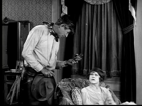 vidéos et rushes de b/w, ms, cu, cowboy (will rogers) placing small crown on daughter's head, woman winking, 1924 - 1924