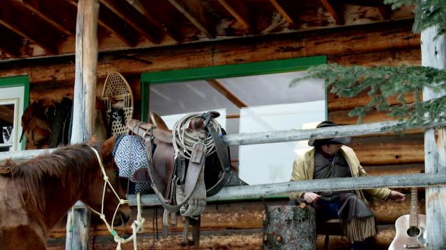 vídeos y material grabado en eventos de stock de cowboy desempeña su guitarra en porche de la cabina. - pórtico