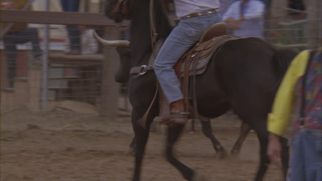 A cowboy pursues a bull in a rodeo ring.