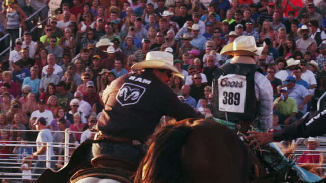 cowboy rides a bucking bronco at a rodeo - shot in slow motion. - 1 minute or greater stock videos & royalty-free footage