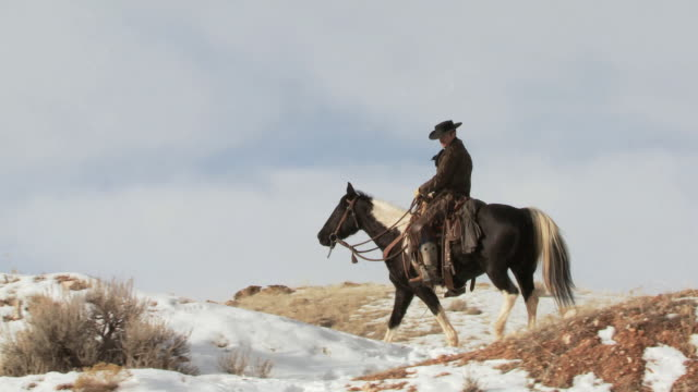 TS Cowboy riding a horse up a snowy ridge / Shell, Wyoming, United States