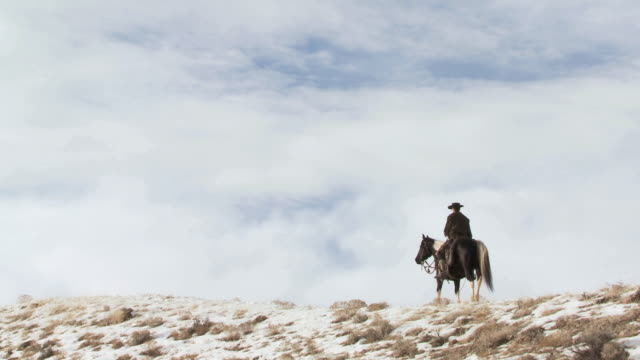 ws cowboy riding horse along snowy ridge / shell, wyoming, united states - newoutdoors stock videos & royalty-free footage