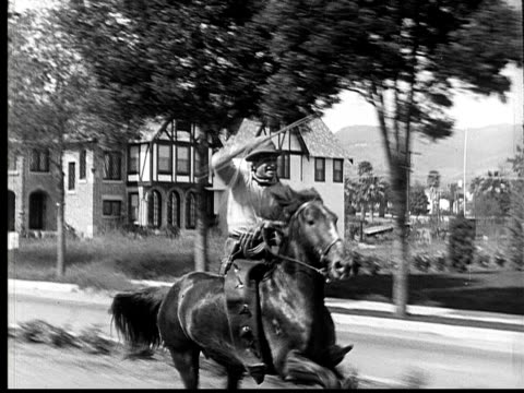 1924 B&W MS cowboy riding horse down residential street spinning lasso above his head