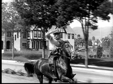 stockvideo's en b-roll-footage met 1924 b&w ms cowboy riding horse down residential street spinning lasso above his head  - alleen één mid volwassen man