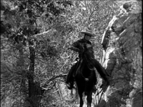 b/w 1921 cowboy (tom mix) riding horse past camera / documentary - 1921 stock-videos und b-roll-filmmaterial