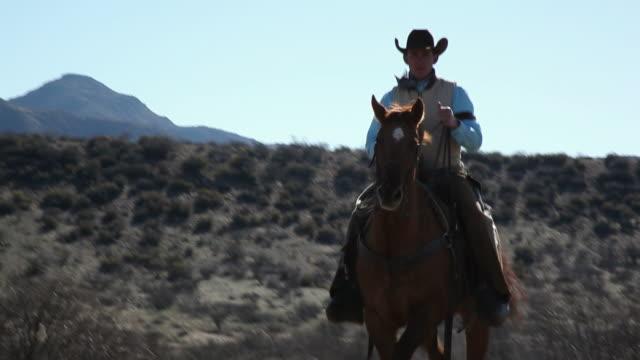 WS TU Cowboy riding on horse / Kirkland, Arizon, USA