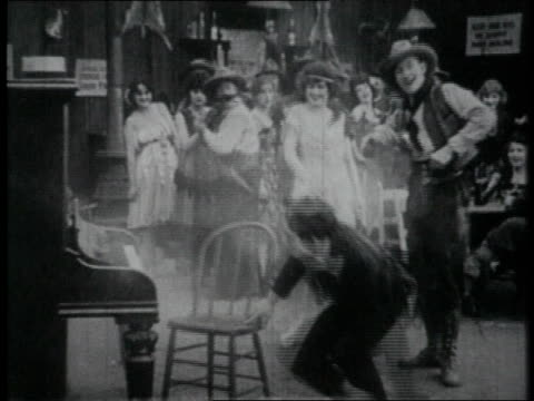 1919 ws cowboy shooting at piano player in saloon - 1910 1919 stock videos & royalty-free footage