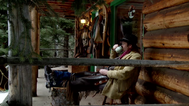 Cowboy sits on porch outside log cabin