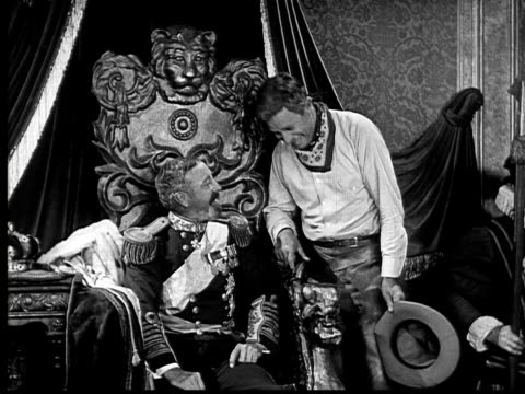 1924 B&W MS cowboy sitting on arm of king's throne, throwing leg over, and whispering to king