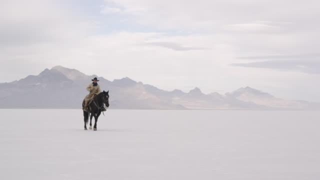 stockvideo's en b-roll-footage met cowboy sitting on horse starting to run on salt flats. - bonneville zoutvlakte