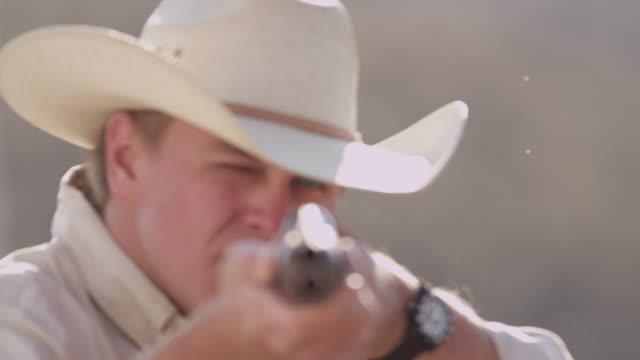 stockvideo's en b-roll-footage met a cowboy squints as he aims a shotgun. - jachtgeweer