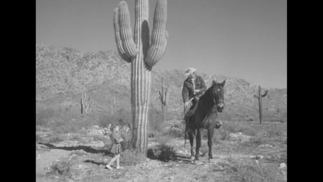 stockvideo's en b-roll-footage met vs cowboy stands on horse next to saguaro cactus as small girl walks up hands him a treat for the horse he feeds it to the horse she is wary of the... - cowboy