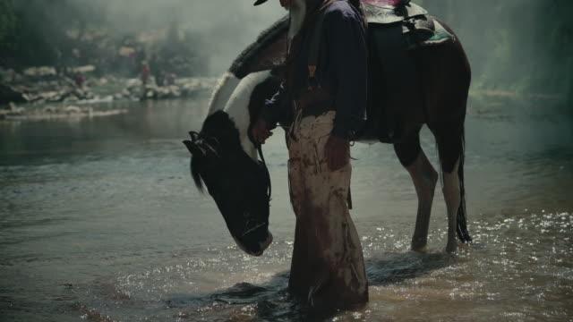 vidéos et rushes de cowboy prendre son cheval à la rivière. - ranch