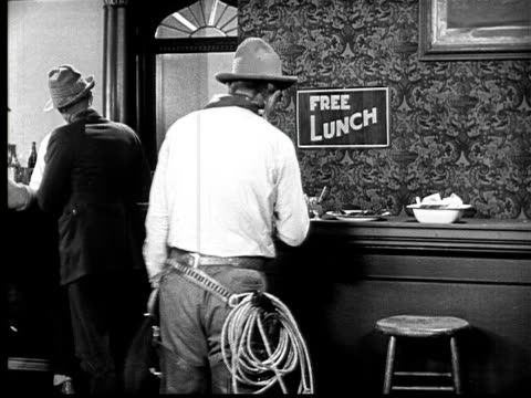 1924 B&W MS cowboy walking up to free lunch counter in bar and gesturing