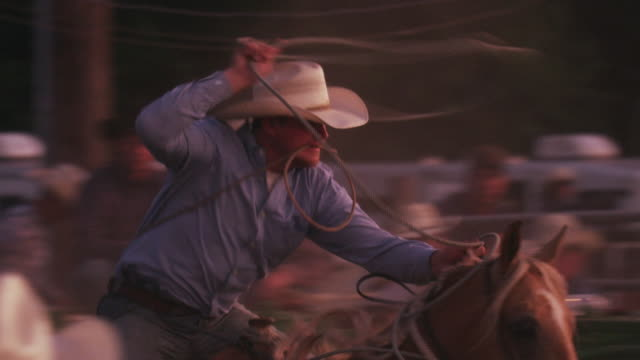 A cowboy with a lariat busts out the chute and attempts to rope a steer - shot in slow motion.
