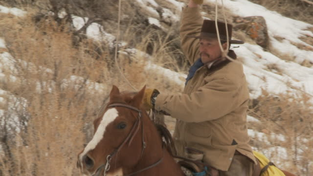 stockvideo's en b-roll-footage met slo mo ms tu cowboy with lasso cantering along in snowy landscape / shell, wyoming, usa - alleen één mid volwassen man