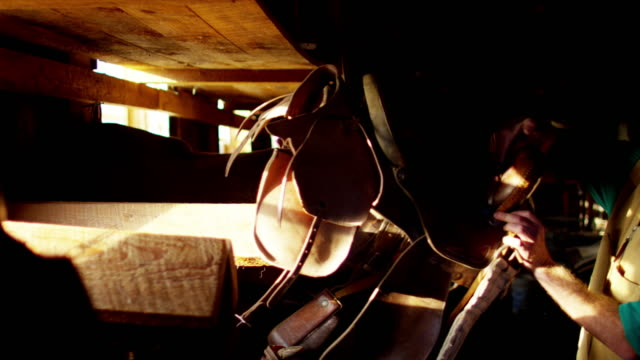 cowboy with saddle in corral barn dude ranch - saddle stock videos & royalty-free footage