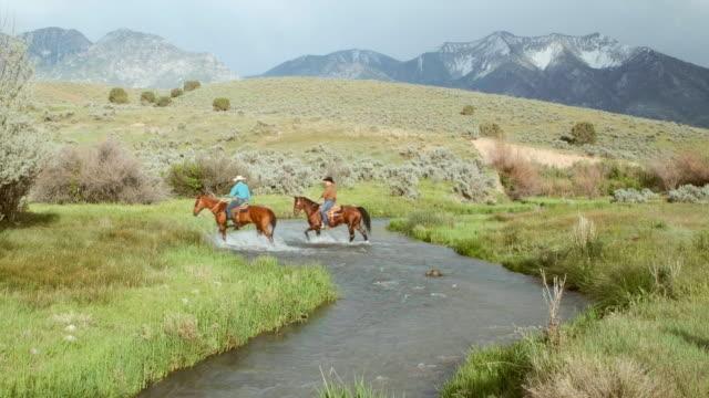 stockvideo's en b-roll-footage met cowboys en cowgirls op paarden - prairie