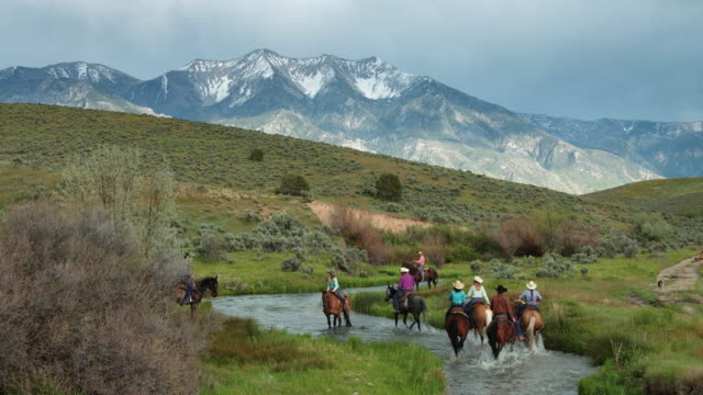 Cowboys and Cowgirls Riding Through River in Idyllic Utah Valley