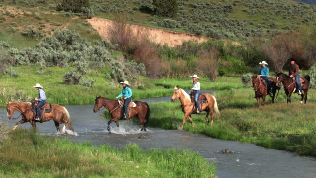 Cowboys and Cowgirls Riding Through River