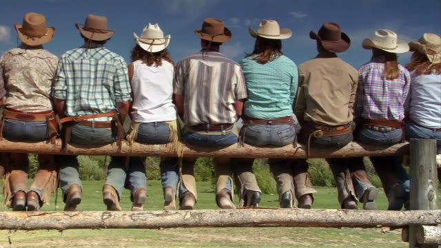 cowboys and cowgirls sit on a split rail log fence near a ranch in encampment, wyoming. - wyoming ranch stock videos & royalty-free footage