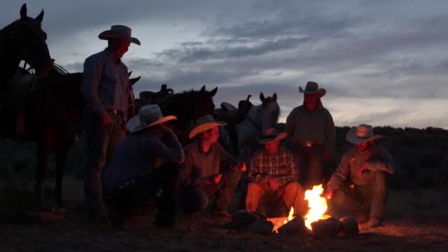 Cowboys around a camp fire.