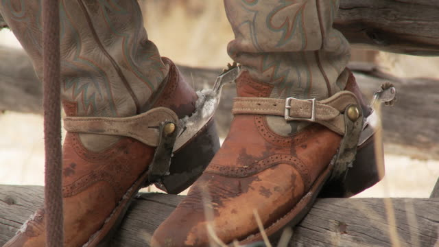 tu cowboy's boots and spurs resting on a fence rail / shell, wyoming, united states - briglia video stock e b–roll