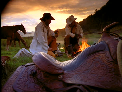 2 cowboys drinking coffee and petting dog by campfire / Horses in background