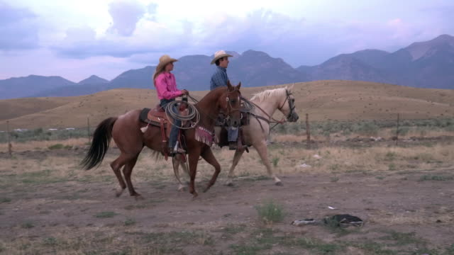 Cowboys driving and rounding up horses.