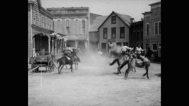 cowboys firing guns while riding horses in town - wild west stock videos & royalty-free footage