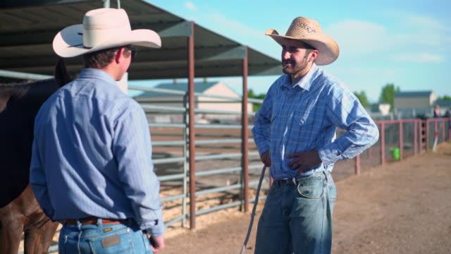 vídeos de stock e filmes b-roll de cowboys getting ready for riding in rodeo arena - cavalgar
