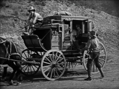 b/w 1924 2 cowboys holding up stagecoach + forcing everyone out at gunpoint / feature - handgun stock videos & royalty-free footage