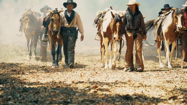 途中で歩いて馬をリードするカウボーイ - 雄馬点の映像素材/bロール