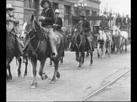 stockvideo's en b-roll-footage met cowboys on horseback approach, pass as they ride in parade for will rogers; stagecoach follows, with rogers inside / side view rogers sits in... - agrarisch beroep