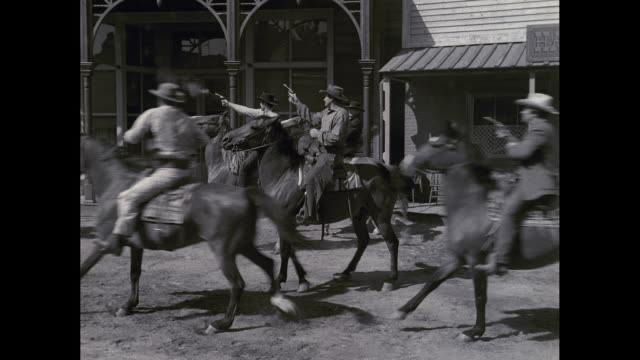 ws pan cowboys on horses firing handguns, falling dead / united states - 1950 stock-videos und b-roll-filmmaterial
