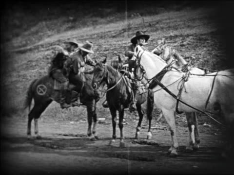 b/w 1924 3 cowboys on horses riding away quickly / feature - pflanzenfressend stock-videos und b-roll-filmmaterial