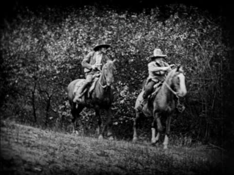 b/w 1924 2 cowboys on horses taking off from hill / feature - pflanzenfressend stock-videos und b-roll-filmmaterial
