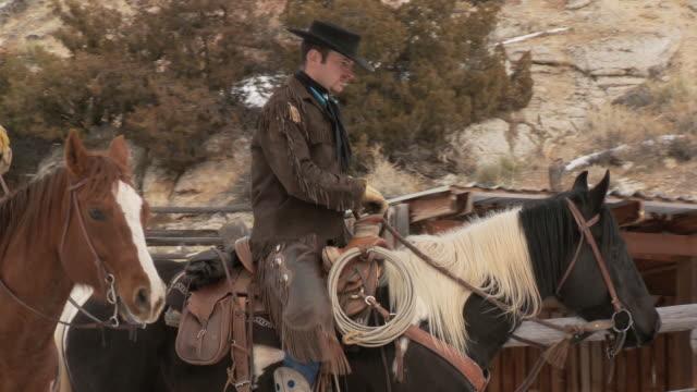 vídeos y material grabado en eventos de stock de ts cowboys riding horses stop and dismount / shell, wyoming, united states - animales de trabajo