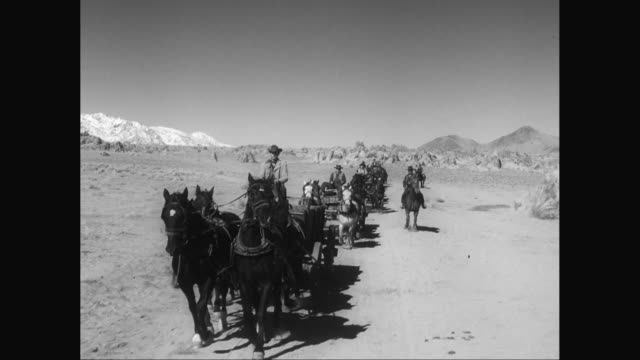 WS POV Cowboys riding in carriages in desert / United States